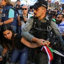 An Israeli policeman tries to take a Palestinian flag from a woman as youth from far-right Israeli groups participate in a flag march at Damascus Gate, just outside Jerusalem's Old City last month