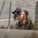A masked man shooting at Palestinians, as a soldier watches on, in Urif in May.