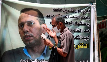 A protester prays by a poster showing Hisham al-Hashimi in Baghdad last year.