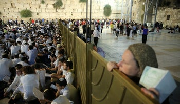 A woman looking across the partition to the men's side at the Western Wall during Tisha B'Av in 2018.