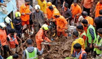 Rescue workers remove debris as they search for survivors after a residential house collapsed due to landslide caused by heavy rainfall in Mumbai, India, earlier today