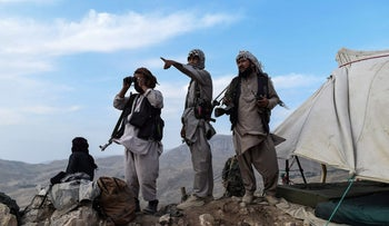 Afghan militia fighters keep a watch at an outpost against Taliban insurgents at Charkint district in Balkh Province, last week.