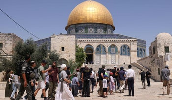 Members of the Israeli security forces stand guard, as a group of Orthodox Jews enter the al-Aqsa mosque compound in Jerusalem, during the annual Tisha B'Av fast, on Sunday.