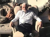 """Hamas leader Yahya Sinwar with his """"victory"""" photograph, sitting in the ruins of his bombed home in the Gaza Strip in May."""