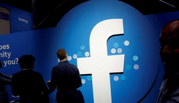Attendees walk past a Facebook logo during Facebook Inc's F8 developers conference in San Jose, 2019.