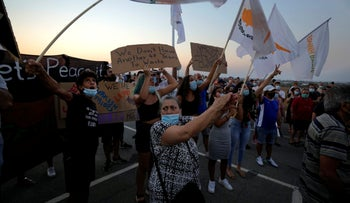 Residents of Varosha hold Cyprus flags and banners during a protest, Monday.