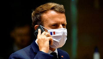 French President Emmanuel Macron speaks on his mobile phone during a round table meeting at an EU summit in Brussels last year