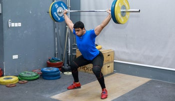 Gaza weight-lifter Mohammad Hamada practices at a gym in Doha, Qatar.