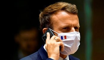 French President Emmanuel Macron speaks on his mobile phone during a round table meeting at an EU summit in Brussels last year.