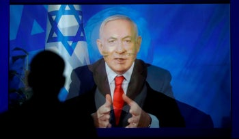 A monitor transitions from a still image to a video satellite feed of then-Prime Minister Benjamin Netanyahu addressing AIPAC in Washington, in 2019.