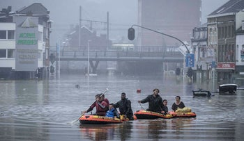 People use rubber rafts in floodwaters after the Meuse River broke its banks during heavy flooding in Liege, Belgium, Thursday, July 15, 2021