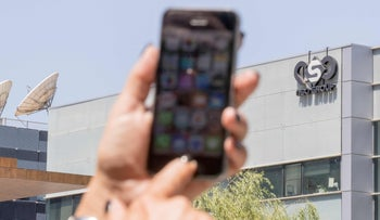 An iPhone is seen with the NSO Group's offices in the background. NSO has denied the database of numbers is linked to them.
