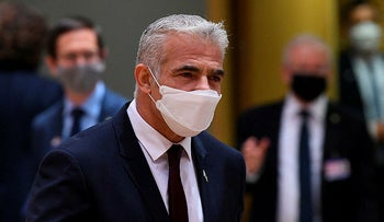 Foreign Minister Yair Lapid arrives for a Foreign Affairs Council meeting at the EU headquarters in Brussels on July 12, 2021.