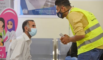A volunteer tries to convince people to get vaccinated against COVID-19 at a medical center in Amman, in May.