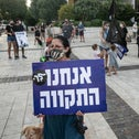 At an anti-Netanyahu protest a woman holds up a sign that reads 'We are the hope.'