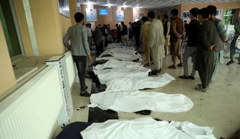 Afghan men try to identify the dead bodies at a hospital after a bomb explosion, last month.
