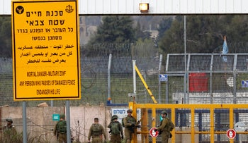 Israeli soldiers stand guard at the Quneitra border crossing of the Israeli Golan Heights, in 2019.