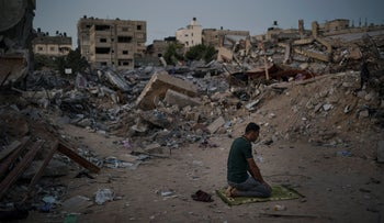 A Palestinian man prays at dusk next to rubble of his family home, destroyed by an airstrike in Beit Lahia, northern Gaza Strip, last month.