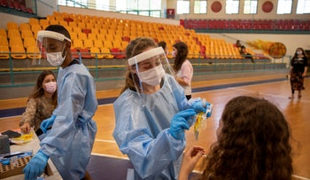 Medical personnel test Israeli youth for the coronavirus at a basketball court turned into a coronavirus testing center, in Binyamina, Israel, last month