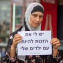 A woman hold a sign that reads 'I have a right to be with my children' at a demonstration for Palestinian reunification rights in El Bireh, on Sunday.