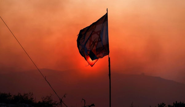 An Israeli flag flutters in the illegal settler outpost of Evyatar, as smoke from fires lit in the nearby Palestinian village of Beita drifts past last month