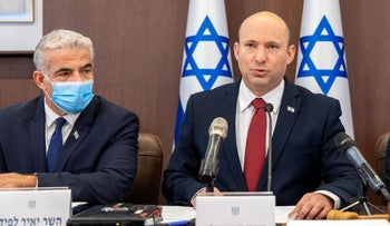 Foreign Minister Yair Lapid (L) and Prime Minister Naftali Bennett (C) at Monday's government meeting