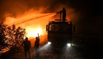 Firefighters pour water as they try to get the fire under control in Kirli village near the town of Manavgat, in Antalya province, Turkey, early Friday July 30, 2021.
