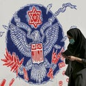 An Iranian woman walks past a mural on the outer walls of the former U.S. embassy in Tehran last year.
