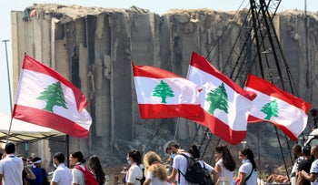 People carry national flags near the site of last year's Beirut port blast, on Wednesday.