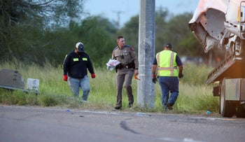 Texas Department of Public Safety pick up debris near a vehicle where multiple people died after the van carrying migrants tipped over just south of the Brooks County community of Encino on Wednesday, Aug. 4