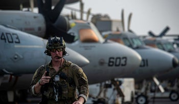 A technician on board the aircraft carrier USS Ronald Reagan responding to a call for assistance from the Mercer Street on July 30, following an attack on it that killed two crew members.