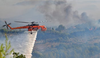 A helicopter dropping water over ancient Olympia, on Thursday.