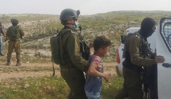 Soldiers arresting Palestinian children for picking flowers near a West Bank settlement in March.