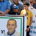 Leith Shurafi holding a mourning poster for his father Shadi, who was killed last week.