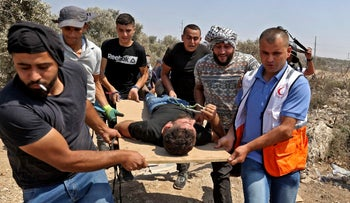 Palestinians carrying a wounded protester near the West bank village of Beita, today.