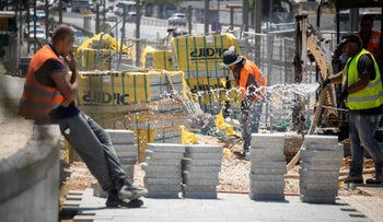 Construction workers in Tel Aviv during Israel's heat wave, on Monday.