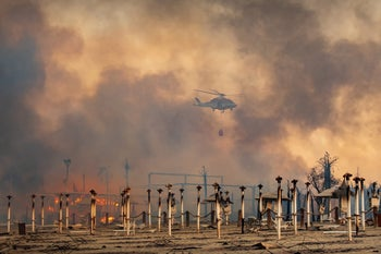 A helicopter carrying water to combat a wildfire on the island of Sicily, Italy, last week.