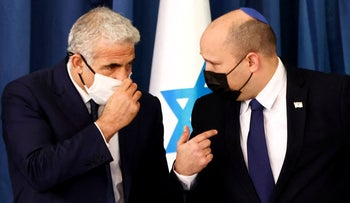 Israel's Prime Minister Naftali Bennett speaks to Foreign Minister Yair Lapid at the weekly cabinet meeting in Jerusalem this week