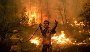 A local resident gestures as he attempts to extinguish forest fires approaching the village of Pefki on Evia (Euboea) island, Greece's second largest island, last week.