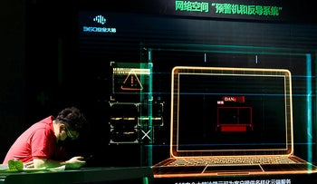 A worker at a computer network security fair waits for visitors near a screen depicting a computer alert system in Beijing on Friday, April 30, 2021.