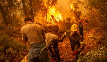 Firefighter and volunteers try to extinguish a fire in the village of Glatsona, Greece, Monday.