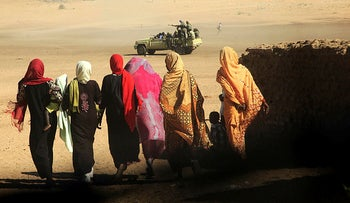 Women and children walk near a truck carrying government troops in the North Darfur region of Sudan.
