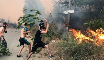 People attempt to put out a fire in the mountainous Tizi Ouzou province, east of Algiers, Algeria August 10, 2021.