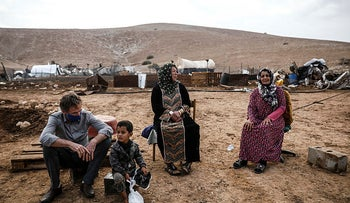Residents of Khirbet Humsa sit in front of the villages' ruins