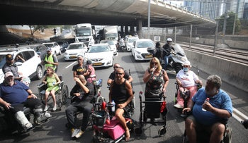 Protesters from organizations representing the disabled block Tel Aviv's Ayalon freeway in July. They were demanding a hike in  government disability grants.