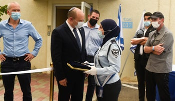 Police Commissioner Kobi Shabtai stands behind Prime Minister Naftali Bennett and an Arab female police officer at Thursday's inauguration ceremony.