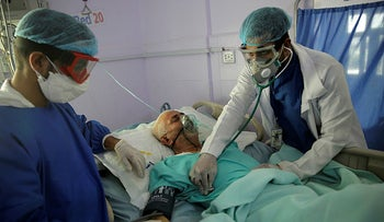 Medical workers attend to a COVID-19 patient in an intensive care unit at a hospital in Sanaa, Yemen, June 2021.