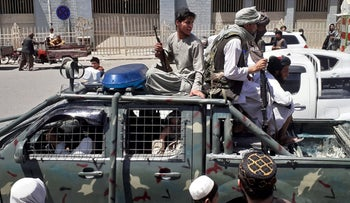 Taliban fighters are pictured in a vehicle of Afghan National Directorate of Security on a street in Kandahar, yesterday.