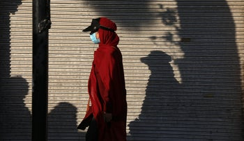 A woman wearing protective face mask to help prevent the spread of the coronavirus walks on a sidewalk in southern Tehran, Iran, last month.