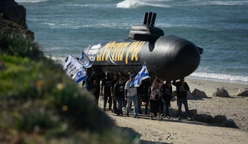 Protesters carry an inflatable submarine, calling on investigators to probe the so-called 'submarine affair,' last year.